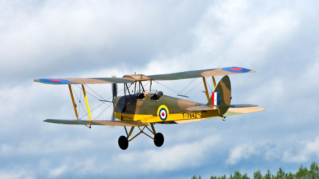 Headcorn Kent England UK - August 13th 2011: An RAF DH82A Tiger Moth bi-plane restored in its original colors in the air at an air display in Kent UK