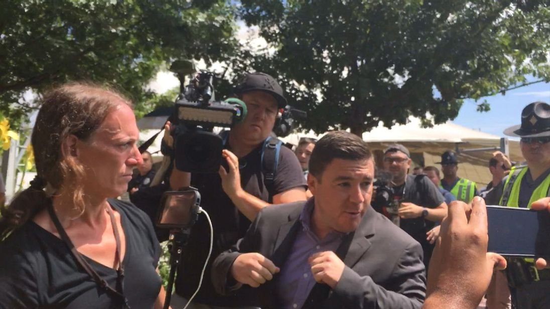 Jason Kessler was heckled and had to be rushed away when protestors stormed the podium.