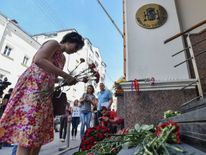 People lay flowers in front of the Spanish embassy in Russia