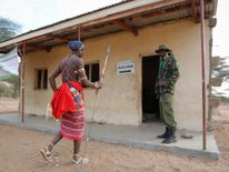A Kenyan Samburu warrior arrives to vote at a polling station in Nkirish.