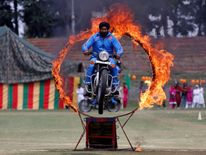 A policeman performs a stunt on a motorbike through a ring of fire