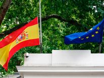A Spanish and an EU flag fly at halfmast above the Spanish Embassy in London