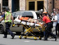 """Rescue workers transport a victim who was injured when a car drove through a group of counter protestors at the """"Unite the Right"""" rally Charlottesville, Virginia"""