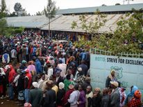 People wait in line to cast their ballot in the general elections at a polling station in Eldoret, Kenya