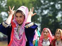 Kashmiri women dance during celebrations marking India's Independence Day