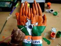 An Indian student gets their palm painted with the Indian national flag and country map