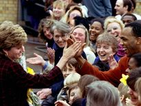 March 1993: Diana gives a high five to Danny Walters, a 29-year-old student onlooker, after her visit to the Riverpoint hostel for women in Southwark, London