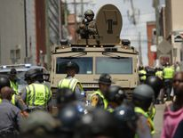 A Virginia State Police officer in riot gear keeps watch from the top of an armored vehicle after car plowed through a crowd of counter-demonstrators
