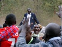 Opposition leader Raila Odinga stands atop of a vehicle outside the Kiberia slums of Nairobi after voting
