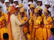 Indian Prime Minister Narendra Modi greets school girls dressed as Hindu Lord Krishna