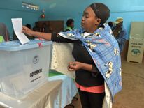 A woman votes in the too-close-to-call battle between incumbent Uhuru Kenyatta and his rival Raila Odinga.
