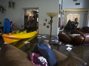 Larry Koser Jr. (L) searching his father's flooded house in west Houston with his son Matthew