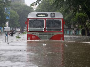 A passenger bus moves through a water-logged road during rains in Mumbai
