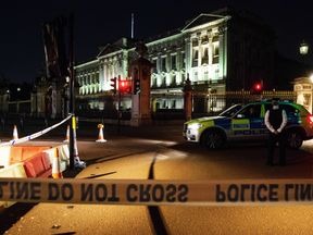 Police teams secure the roads around Buckingham Palace following the attack on Friday night