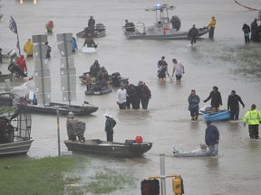 People walk down a flooded street as they evacuate their homes in Houston, Texas