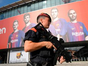 An armed Catalan policeman outside the Camp Nou stadium ahead of the Barcelona vs Real Betis match