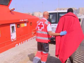 A Red Cross worker leads away a migrant