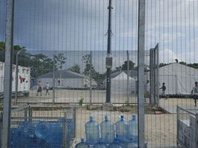 Detainees walk around the compound among water bottles inside the Manus Island detention centre in Papua New Guinea
