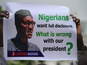 A protester shows a placard in the rain during a protest to demand that ailing President Mohammadu Buhari resume work or resign in Abuja, on August 7, 2017