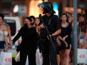 A policeman stands guard after a van deliberately drove at a crowd in a busy tourist district