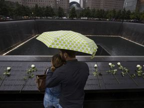 A couple stand under an umbrella at the national 9/11 memorial in Manhattan. File pic