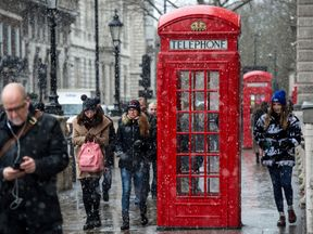 Tourists walk past a red phone box as snow falls on Parliament Square on January 13, 2017 in London, United Kingdom