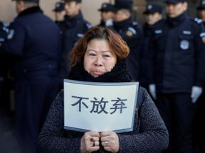 """A relative of an MH370 passenger at the Foreign Ministry in Beijing with a placard reading: """"Don't give up"""""""