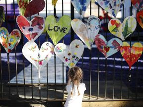 A young girl adds finishing touches to paper hearts adorning a fence in Kensington, near the burnt-out remains of Grenfell Tower in London on August 25, 2017 ahead of the Notting Hill Carnival.