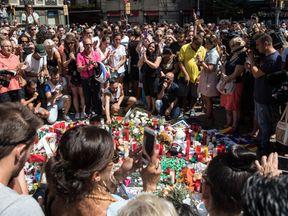 People gather around tributes laid on Las Ramblas