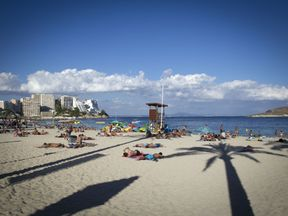 Tourists sunbath at Magaluf's beach in Calvia on Mallorca Island on August 10, 2015. AFP PHOTO/ JAIME REINA (Photo credit should read JAIME REINA/AFP/Getty Images)