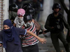 Demonstrators run from security forces during a protest in Caracas