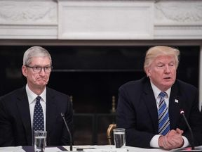 Apple CEO Tim Cook listens to US President Donald Trump during a tech summit  at the White House in June