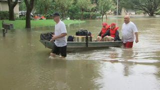 One couple, along with their cat, are ferried to safety by a neighbour and his boat