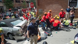 A woman is received first-aid after a car accident ran into a crowd of protesters in Charlottesville