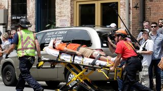 "Rescue workers transport a victim who was injured when a car drove through a group of counter protestors at the ""Unite the Right"" rally Charlottesville, Virginia"