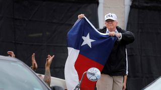 Donald Trump holds a flag of the state of Texas after receiving a briefing on Tropical Storm Harvey relief efforts