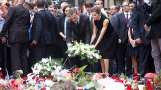 Spain's King Felipe and Queen Letizia place flowers at memorial site