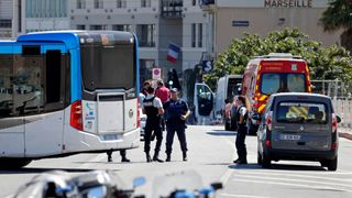 French police secure the area in Marseille, where one person was killed and another injured after a car crashed into two bus shelters