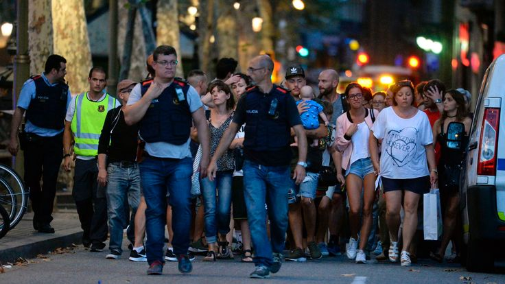 Plain clothes policemen escort people away from the scene in Barcelona