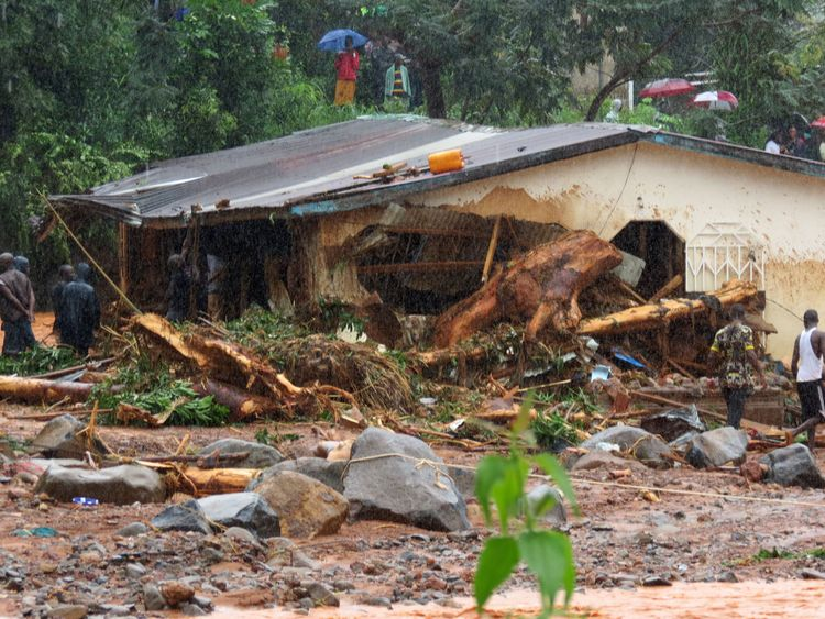 TOPSHOT - Bystanders and rescue personnel gather beside a flood damaged building in an area of Freetown on August 14, 2017, after landslides struck the capital of the west African state of Sierra Leone. At least 312 people were killed and more than 2,000 left homeless when heavy flooding hit Sierra Leone's capital of Freetown, leaving morgues overflowing and residents desperately searching for loved ones. An AFP journalist at the scene saw bodies being carried away and houses submerged in two ar