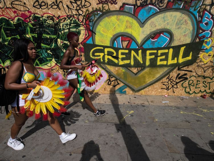 Performers walk past graffiti marking the Grenfell tragedy
