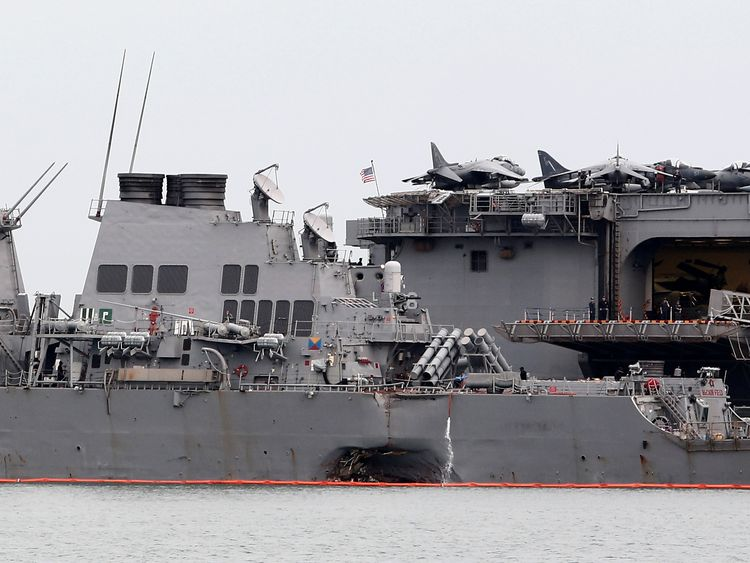 he damaged USS John McCain is docked next to USS America at Changi Naval Base in Singapore