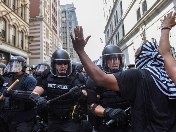 Boston Police officers react as a crowd of counter protesters clashes with them outside of the Boston...