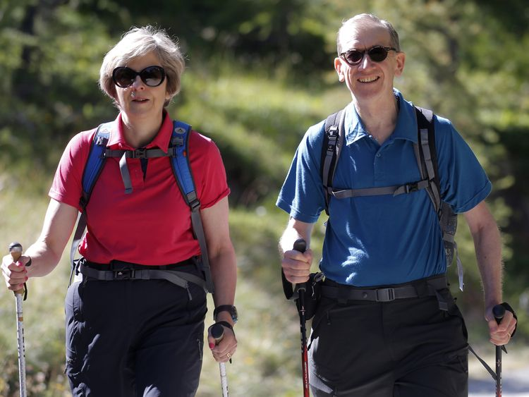 British Prime Minister Theresa May walks with her husband Philip John May while on summer holiday on August 12, 2016 in the Alps of Switzerland