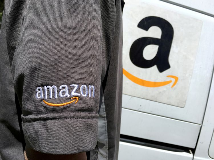 An Amazon.com Inc driver stands next to an Amazon delivery truck in Los Angeles, California, U.S. on May 21, 2016