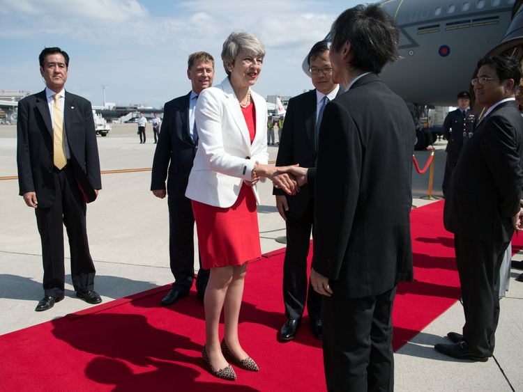 Prime Minister Theresa May is greeted by dignitaries as she arrives in Japan