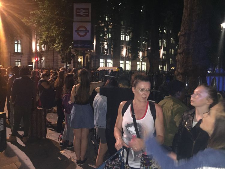 Passengers wait on the area outside Euston station after a security alert
