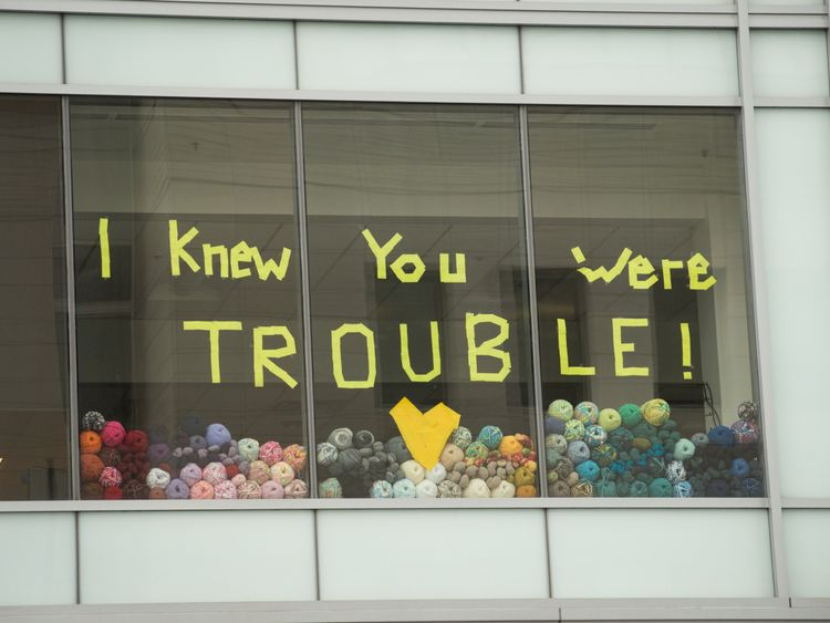 A message from a Taylor Swift lyric is displayed on a window opposite the court house