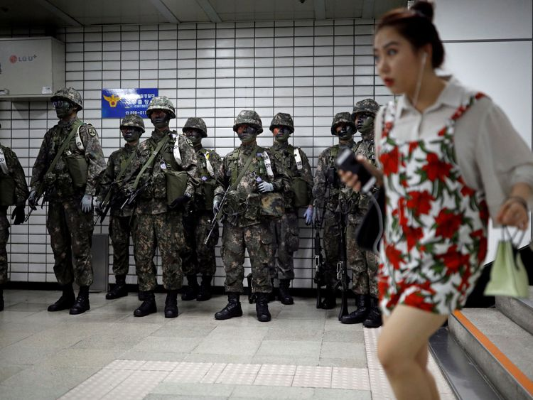 A woman walks past South Korean soldiers as they look on during an anti-terror drill as part of the Ulchi...