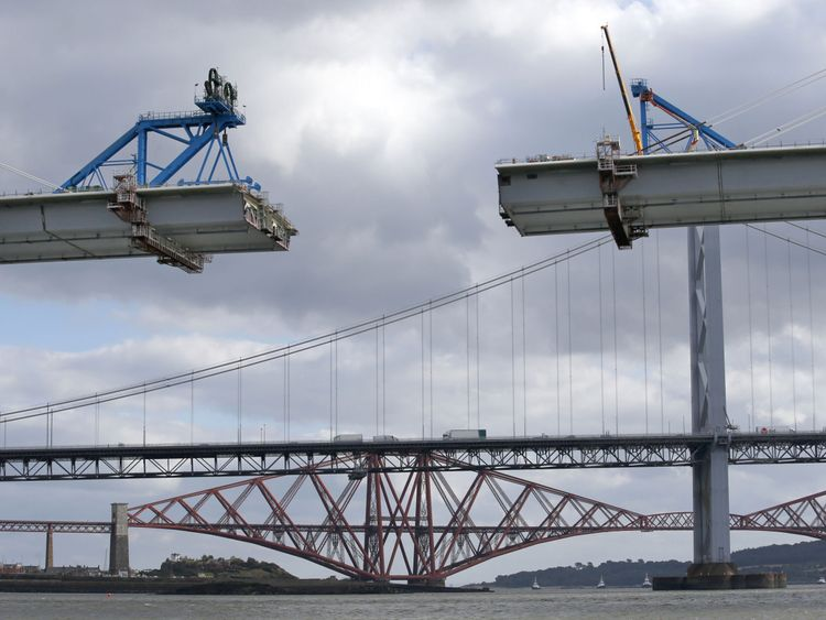 View of the gap between the north and central sections of the road deck of the new Queensferry Crossing, with the old Forth Road and Forth Railway bridges in the background